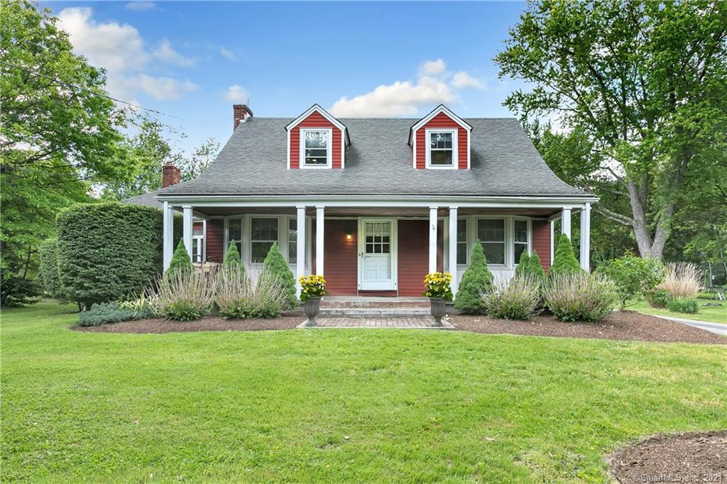 Beautiful red house with front porch on a green lawn